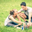 Happy couple training in the park - Young man and woman during summer workout and sport activity - Male and female fitness models stretching leg muscles after running - Vintage filtered look — Stock Photo