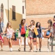 Group of happy best friends with shopping bags in the city center - Tourists walking and having fun in the summer around the old town - University students during a break in a sunny day — Stock Photo #50208721