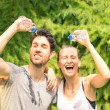 Sporty couple refreshing with cold water after run training in the park - Sport fitness young happy models taking a break after jogging in the nature — Stock Photo #50208799
