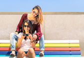 Best friends enjoying time together outdoors with smartphone - Concept of new technology with two girlfriends having fun on a multicolored bench — ストック写真