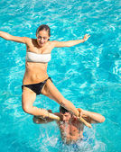 Happy young couple in swimming pool jumping from the shoulder - Concept of love and fun with joyful moments in summer - Vacation lifestyle in exclusive hotel resorts — Stock Photo