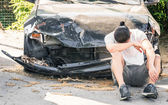 Desperate man crying on his old damaged car after a crash accident — 图库照片