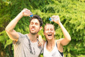Sporty couple refreshing with cold water after run training in the park - Sport fitness young happy models taking a break after jogging in the nature — Stock Photo