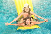 Best friends in bikini enjoying time together outdoors in swimming pool - Concept of freedom and happiness with two girlfriends having fun in the summer — Stock Photo