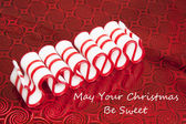 Old Fashioned Merry Christmas Ribbon Candy on Red Background Greeting — Stock Photo