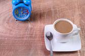 Tasse und Uhr auf einem Holztisch — Stockfoto