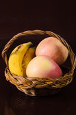 Apples and bananas in the basket on black background — Stock Photo