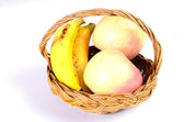 Apples and bananas in the basket on white background — Stock Photo