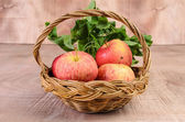 Apple and Asiatic in basket on wood background — Zdjęcie stockowe