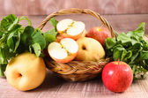Apple and Asiatic in basket on wood background — Stock Photo