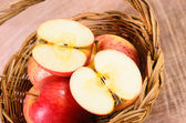 Apples in basket on a wood background — Stock Photo