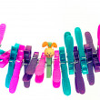 Colorful character plastic pegs on a line — Stock Photo