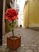 Artificial red rose in support on street — Stock Photo