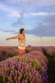 Girl walking in a lavender field during sunset — Stock Photo