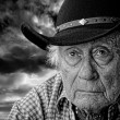 Stock Photo: Old cowboy against a stormy sky