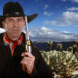 Cowboy with gun touching hat in cholla garden — Stock Photo