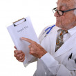 Kind old doctor pointing at chart — Stock Photo