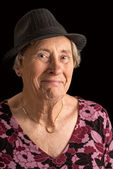 Senior lady wearin a fedora with an amused look on her face — Stock Photo