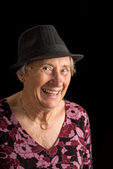 Senior lady wearing a fedora laughing — Stock Photo
