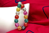Perles multicolores sur fond rouge — Photo