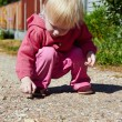 Little girl plays with pebbles — Stock Photo