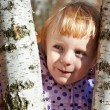 Cunning little girl with birch — Stock Photo #34223051