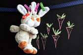 Chalkboard with carrots and toy rabbits — Stock Photo