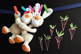 Chalkboard with Drawing and toy rabbits — Stock Photo