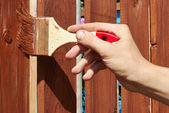 Painting wooden fence with a brown paint — Stok fotoğraf