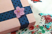 Present box  with a blue ribbon and  a violet flower — Stock Photo