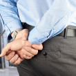 Businessman standing with hands behind — Stock Photo
