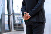 Businessman  standing  with both   hands behind — Stock Photo