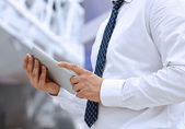 Businessman  standing  and holding  digital tablet  — Stock Photo