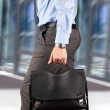 Businessman walking and holding  a  leather briefcase in his han — Stock Photo #47324611