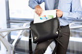 Businessman holding and geting out   documents with graphs  from — Stock Photo