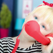 Pretty little blond girl with a red retro phone — Stock Photo