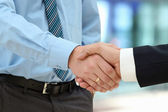 Close-up image of a firm handshake  between two colleagues in of — Stock Photo