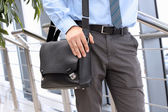 Businessman standing  and holding  a  leather briefcase on his s — Stock Photo