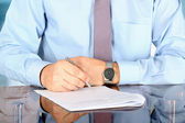 Businessman  sitting at office desk and  signing a contract  by — Stock Photo