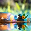 Three candles and towels black stones and orange daisy on water — Stock Photo