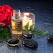 Wellness oil, red flower, stones and candle — Stock Photo