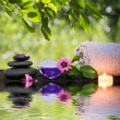Two candles and towels black stones and purple flower on water — Stock Photo