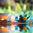 Three candles and towels black stones and orange daisy on water — Stock Photo #29980995