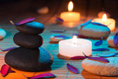 White and black stones, purple petals, and candles — Stock Photo