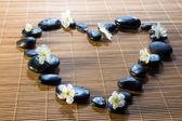 Serce z czarne kamienie i kwiaty na mat bambusowych — Zdjęcie stockowe