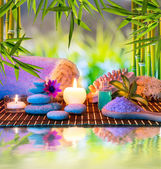 Massage in the bamboo garden with violet flowers, candles — Stock Photo