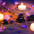 Black stones, violet flowers, and candles on mat bamboo — Stock Photo