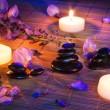 piedras negras, violetas flores y velas en la estera de bambú — Foto de Stock