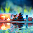 Two candles and towels black stones and tiare on water — Stock Photo