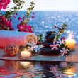 Candles - black stones and tiare - Bougainvillea on water — Stock Photo